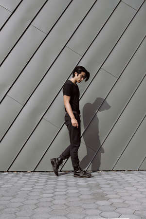 Asian male model posing walking, long dark haircut, wearing black t-shirt and jeans on the grungy background, model test shoot