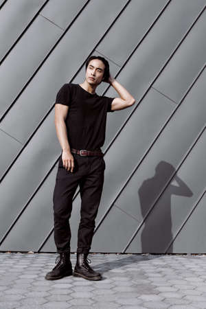Asian male model posing, long dark haircut, wearing black t-shirt on the grungy metal background, model test shoot, straightens hair with hand