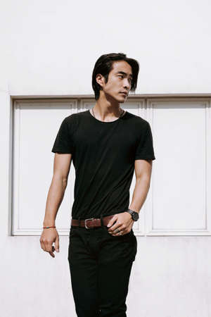 Asian male model posing, confident look, white concrete wall background, hand on the belt, long dark haircut, wearing black t-shirt and jeans, model test shoot