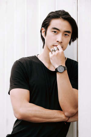 Asian male model posing arms crossed thinking, hand touches face, confident look, leaning against the white wall, long dark haircut, wearing black t-shirt, model test shoot Фото со стока