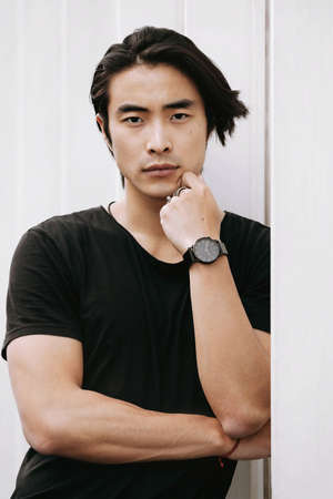 Asian male model posing arms crossed thinking, hand touches face, confident look, leaning against the white wall, long dark haircut, wearing black t-shirt, model test shoot