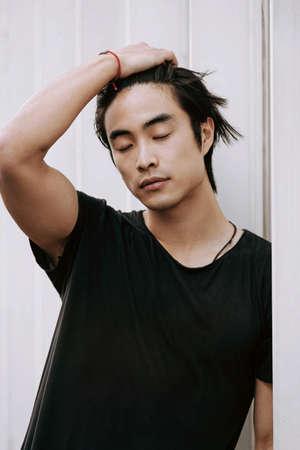 Asian male model posing, long dark haircut, wearing black t-shirt on the white minimal background, model test shoot, straightens hair with hand