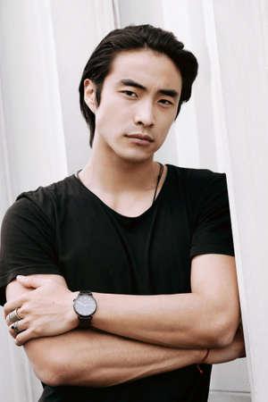 Asian male model posing arms crossed, long dark haircut, wearing black t-shirt on the white minimal background, model test shoot
