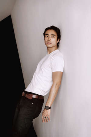 Asian male model posing leaning back against the wall, long dark haircut, wearing white t-shirt on the minimal white wall background, model test shoot