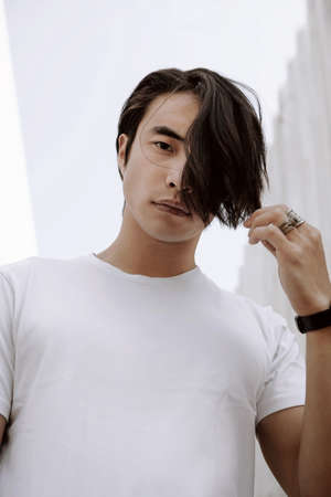 Asian male model posing, long dark haircut, wearing t-shirt on the white minimal background, model test shoot, touches hair with hand