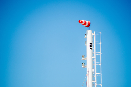 moderate: Frayed windsock in moderate wind against blue sky with few clouds Stock Photo