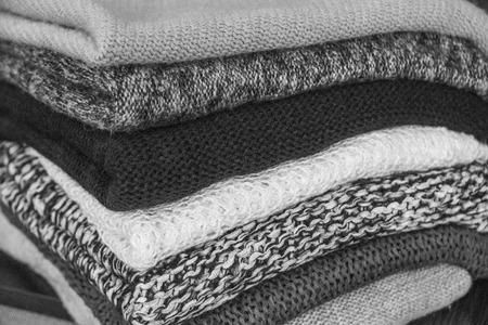 knitwear: Pile of knitted winter clothes on wooden background, sweaters, knitwear, space for text black and white