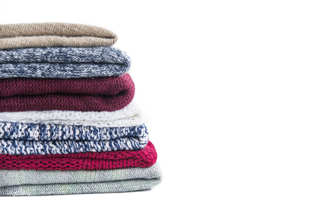 warm clothing: Pile of knitted winter colored clothes on wooden background, sweaters, knitwear, space for text