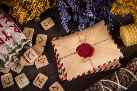 Mazzo Di erba secca che di solito viene utilizzato in più rituale, magico e pulizia, rune, vecchia busta con il timbro cera e candele Archivio Fotografico - 60727412