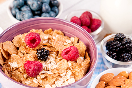 healthy breakfast with cornflakes berries, milk and nuts on wooden table Standard-Bild