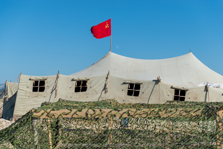 soviet flag: very big military tent in the field with red soviet union flag Stock Photo