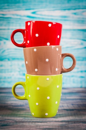 Several colorful tea cups on vintage background
