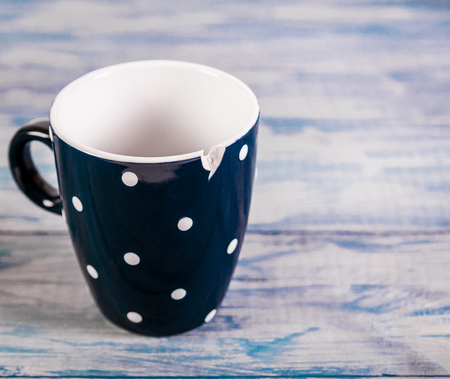 Broken black ceramic cup, blue wooden background, free space