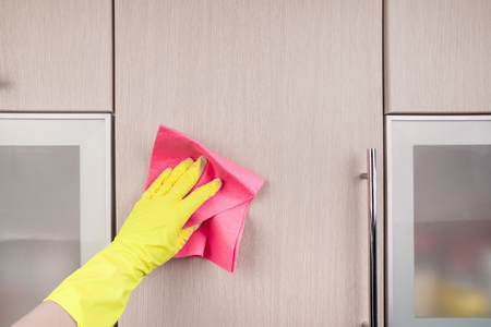 dirt: Hand in protective glove cleaning wooden furniture with rag. Early spring cleaning or regular clean up. Maid cleans house.