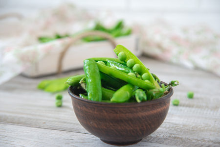 bean family: Pods of green peas outside on a wooden table Stock Photo