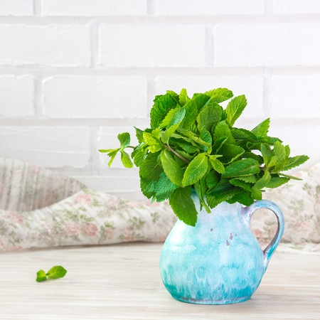 cerulean: sheaf of fresh mint leaf on rustic background. Copy space. Stock Photo