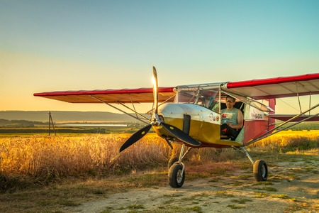 A crop duster applies chemicals to a field Editorial
