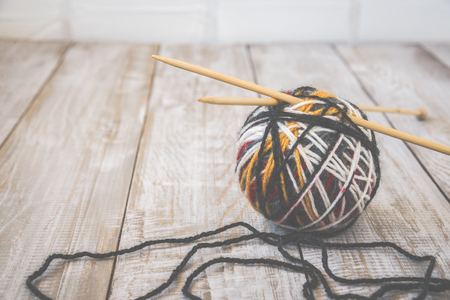 Retro photo of modern color ball of wool with knitting bamboo needles. Toned