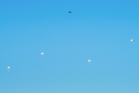 Airborne troops a mass parachute drop over the sea. On a blue sky background Imagens