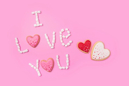 Marshmallows on pink background with sign in English I Love You. Flat lay or top view. Background or texture of colorful mini marshmallows. Gingerbread hearts. Valentines day background concept