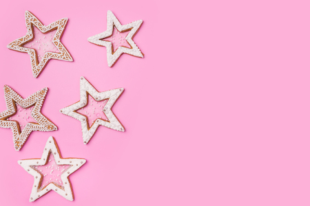 Christmas gingerbreads stars on sweet pink background.Top view image. Copyspace for your text