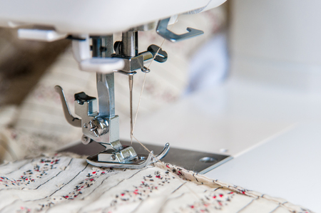Modern Sewing machine with light flower pattern fabric Archivio Fotografico