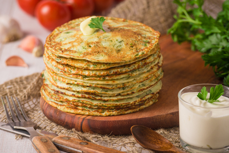 Many pancakes with fresh herbs and sour cream sauce on a wooden table. Traditional Ukrainian or Russian pancakes. Maslenitsa. Traditional dishes on the holiday Carnival Maslenitsa Shrovetide. Rustic style photo