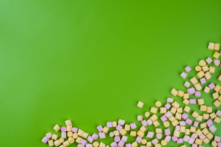 Marshmallows on green background with copyspace. Flat lay or top view. Background or texture of colorful mini marshmallows. Winter food background concept.