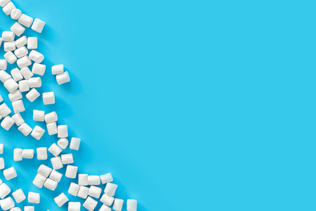Marshmallows on blue background with copyspace. Flat lay or top view. Background or texture of colorful mini marshmallows. Winter food background concept