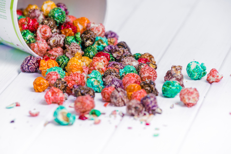 Brightly Colored Candied Popcorn, white background. Horizontal image of Junk food, fruit flavored popcorn in light pink bowl. Colorful, rainbow, candy coated popcorn. Shallow focus on popcorn in bowl Archivio Fotografico