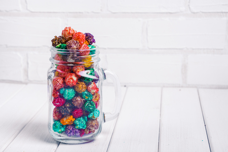 Brightly Colored Candied Popcorn, white background. Horizontal image of Junk food, fruit flavored popcorn in glass jar mason. Colorful, rainbow, candy coated popcorn. Shallow focus on popcorn in bowl On the wooden table, selective focus and copyspace. Banco de Imagens