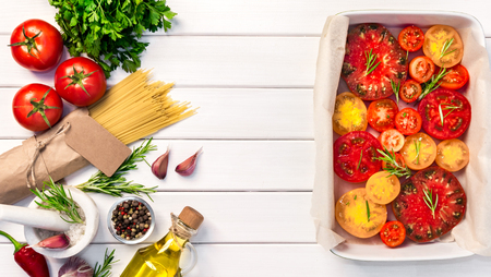 Fresh organic ingridients, pasta spaghetti of italian recipes. Tomatoes with rosemary into ceramic. Healthy food concept on white wooden table background. Top view, copy space.
