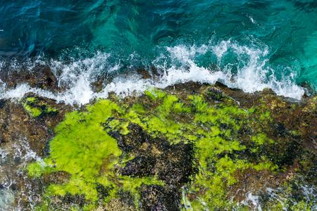 rock in the sea, blue waves, rocks, foam, raging sea, spray, top view down. 版權商用圖片