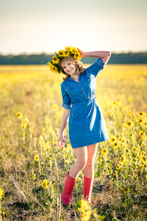 Cute redhaired happy smiling girl in the field full of sunflowers, wreath of sunflowers. dressed in a dress-shirt made of denim and red rubber boots.
