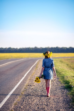 Beautiful elegant woman walking on a country road. Cute redhaired girl in the field full of sunflowers, wreath of sunflowers and bouquet of sunflowers, dressed in a dress-shirt made of denim and red rubber boots. Banque d'images
