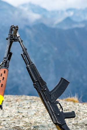 Assault rifles on the background of the Caucasus mountains. Stock Photo