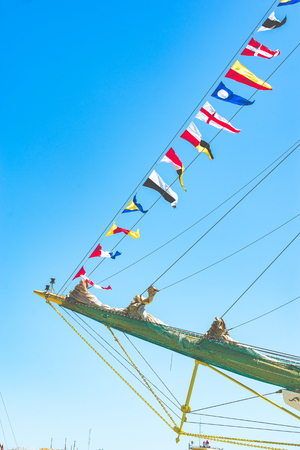 Colorful nautical sailing flags flying in the wind from the lines of a sailboat mast backlit in bright blue sky by the sun.