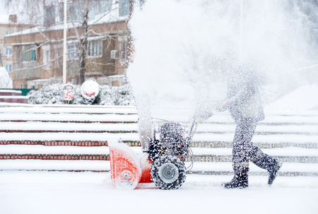 Snow-removal work with a snow blower. Man Removing Snow. heavy precipitation and snow piles Stock Photo