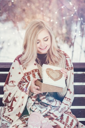 Smiling young woman with christmas present box in a blanket in a country house