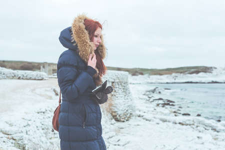 Girl in a warm jacket with fur stands on the frozen bank of the winter sea