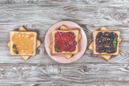 Delicious toasts with various sweet jams on grey background. Copyspace for your text, banner