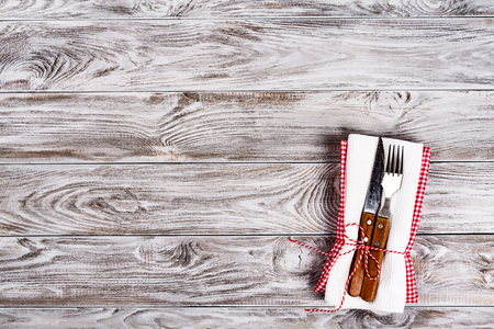 Empty wooden table background and fork and knife on napkin. Dinner, lunch or breackfast concept Archivio Fotografico