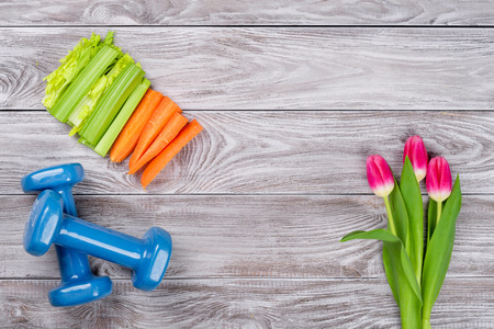Spring flatlay sports composition with celery an carrots blue dumbbells and tulips on gray wooden background. Concept healthy lifestyle, sport and diet in spring. Top view