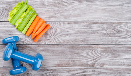 Spring flatlay sports composition with celery an carrots blue dumbbells on gray wooden background. Concept healthy lifestyle, sport and diet in spring. Top view 写真素材