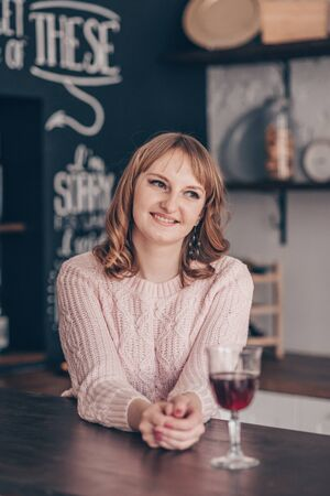 Happy smiling woman with glass of redwine at family kitchen. Archivio Fotografico - 130177568