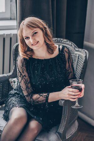 Beautiful young caucasian European woman sitting in an armchair. Archivio Fotografico - 130177585
