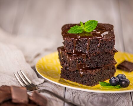 A stack of chocolate brownies on wooden background with mint leaf on top, homemade bakery and dessert.