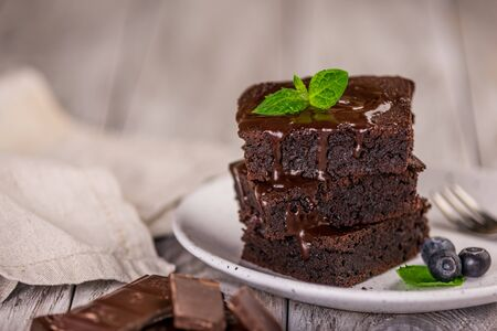 A stack of chocolate brownies on wooden background with mint leaf on top, homemade bakery and dessert Stock Photo