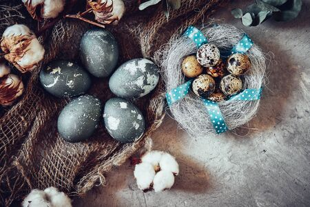 Easter eggs and cotton flowers on grey stone background