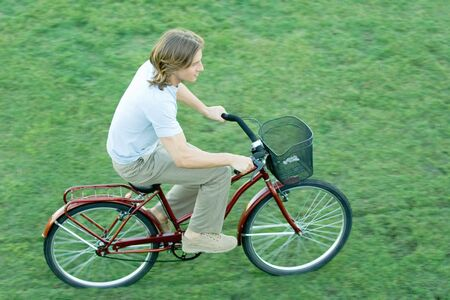 Young man riding bicycle across grass LANG_EVOIMAGES